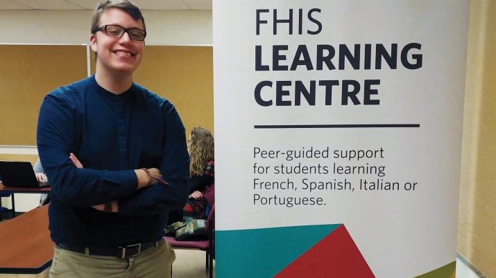 Joseph Bouchard standing beside FHIS Learning Centre banner