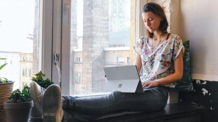 Woman working on iPad while sitting on the window sill