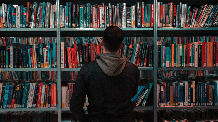 Man looking at a shelf of books.