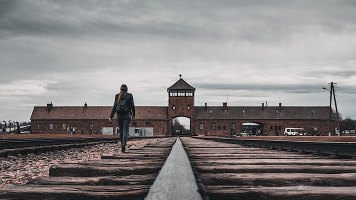 Person walking through Auschwitz concentration camp in Poland.